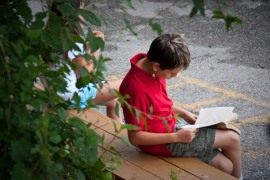 Middle School Student Reading Outside at Oneness-Family School